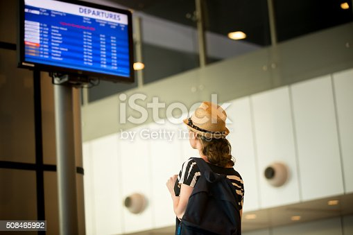 469824732istockphoto Woman in front of airport flight information panel 508465992