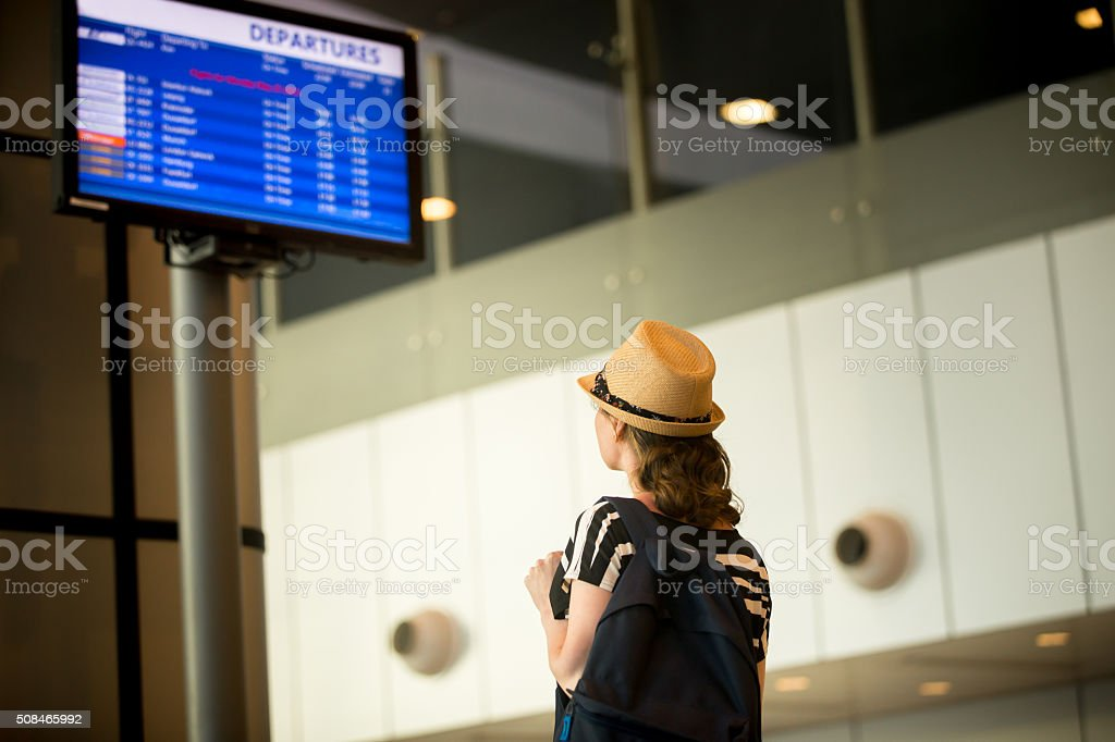 Woman in front of airport flight information panel stock photo