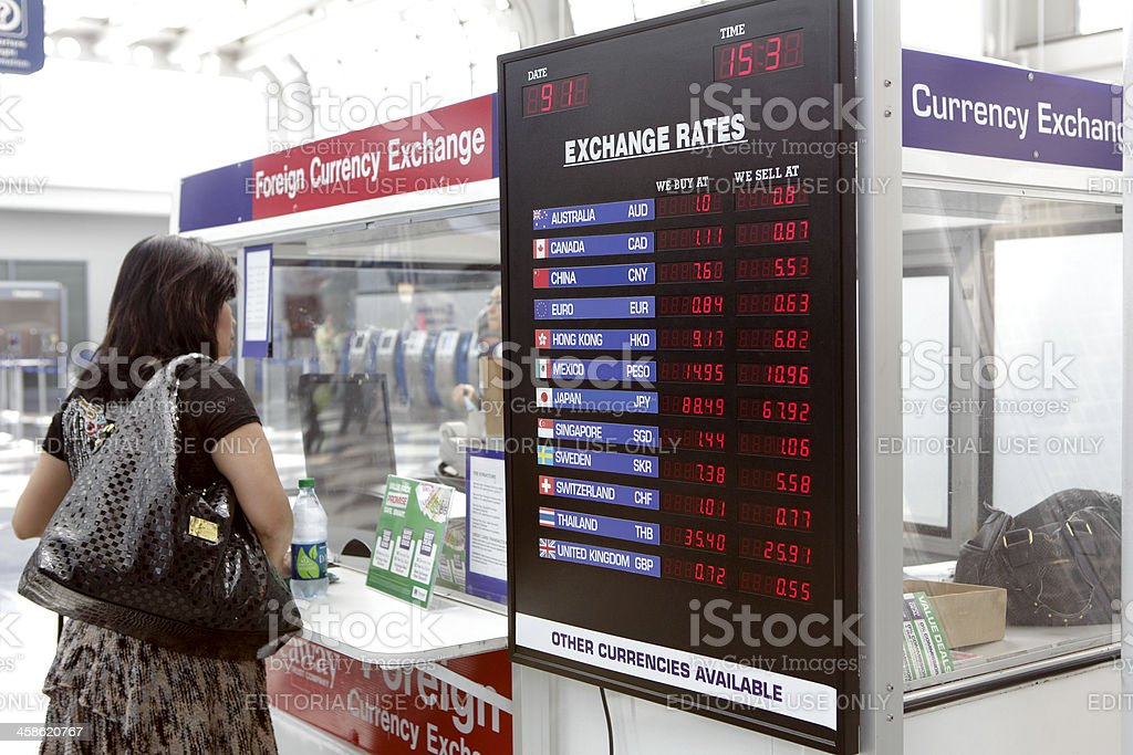 Woman in front of foreign currency exchange kiosk stock photo