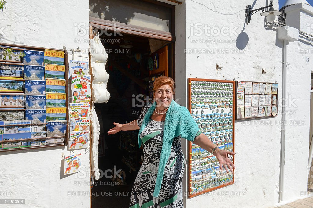 Woman in front of her souvenir shop of Alberobello stock photo