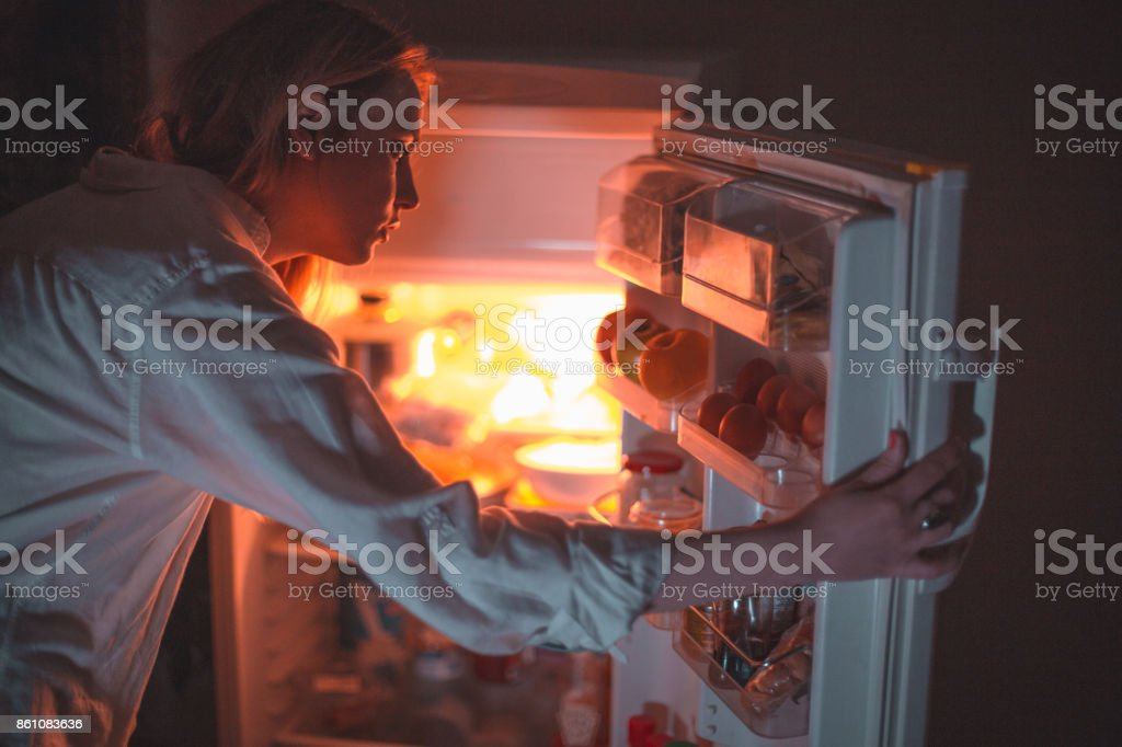 Woman in front of the refrigerator late night stock photo