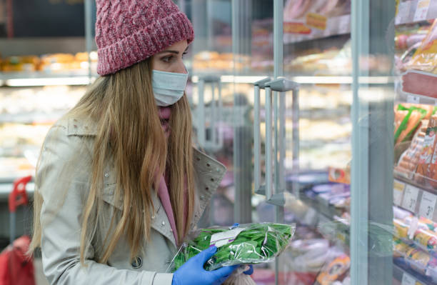 Woman in full corona outfit shopping in supermarket stock photo