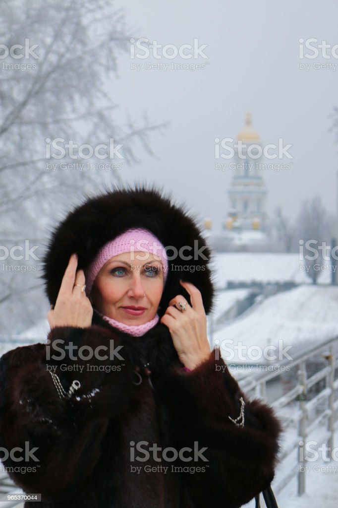 Woman in fur hood on the winter footbridge looks mysteriously to the left zbiór zdjęć royalty-free