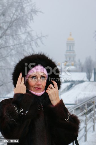 Woman In Fur Hood On The Winter Footbridge Looks Mysteriously To The Left Stock Photo & More Pictures of Adult
