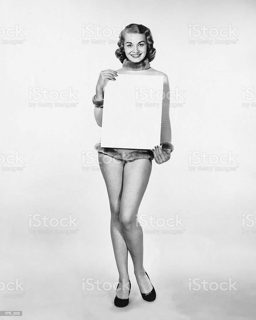 Woman in fur-trimmed leotard holding blank poster royalty free stockfoto