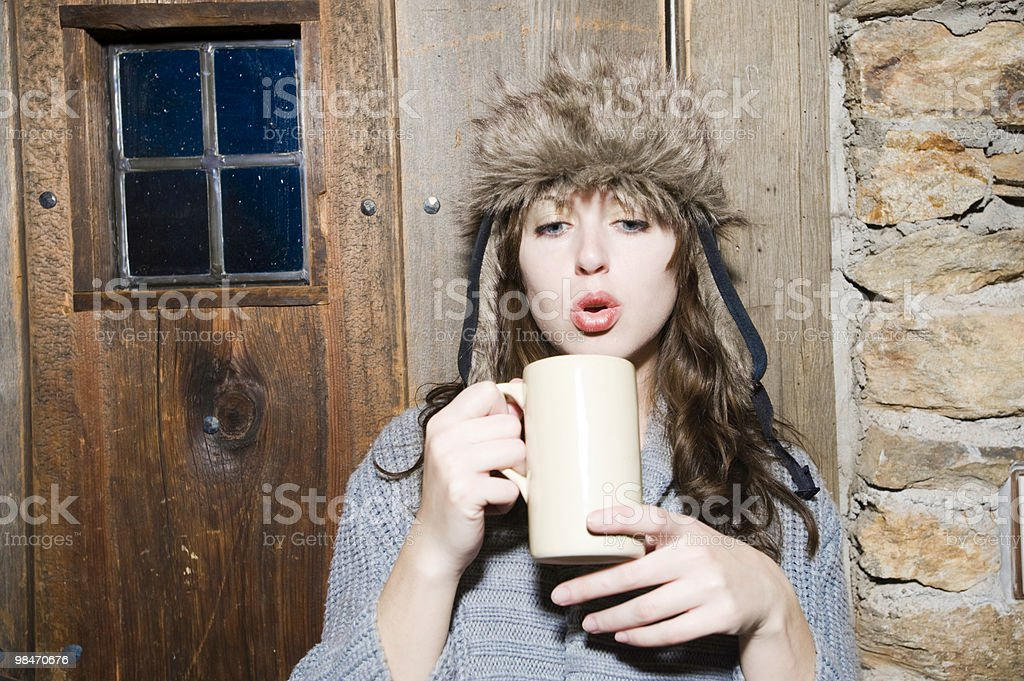 Woman in fury hat blowing on hot coco stock photo