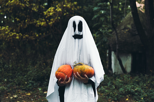 Woman dressed like a spooky smiling ghost holding two beautiful orange pumpkins and staying in the scary forest near abandoned house celebrating Halloween