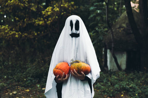 Woman in ghost costume with pumpkins wish you a Happy Halloween! stock photo