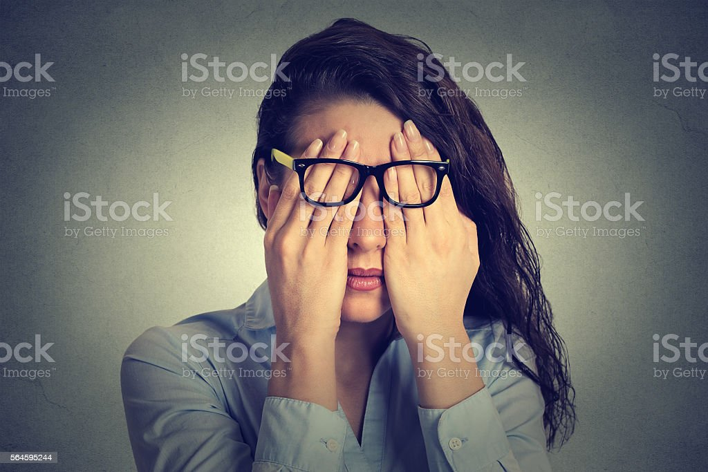 woman in glasses covering face eyes with two hands stock photo
