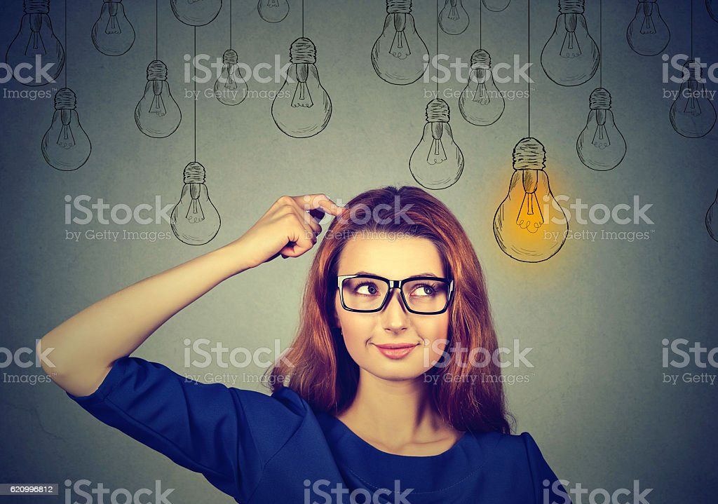 woman in glasses looking up at light idea bulb stock photo