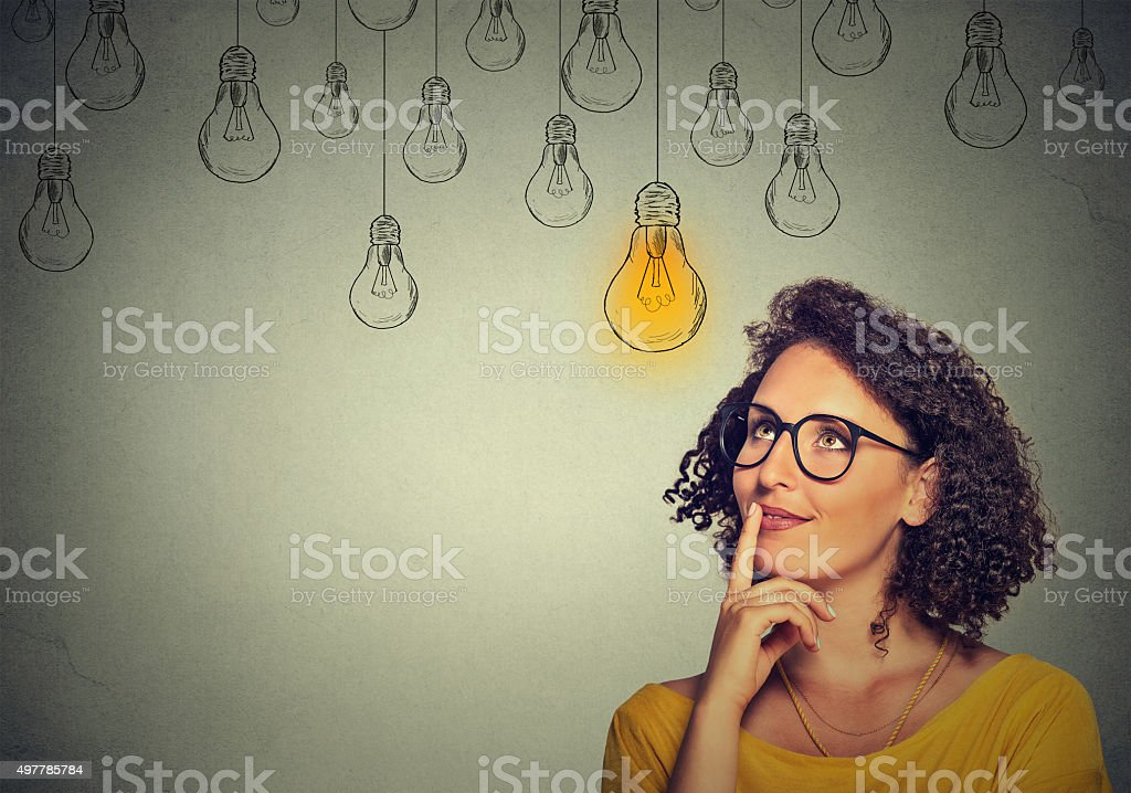 Portrait thinking woman in glasses looking up with light idea bulb...