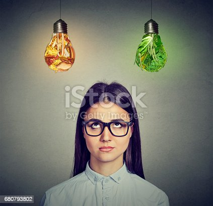 istock Woman in glasses thinking looking at junk food and green vegetables light bulb 680793802