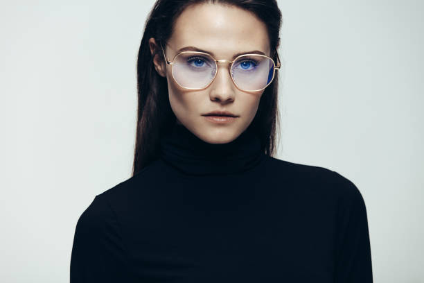 Woman in glasses with intense expression Close up portrait of woman wearing glasses staring with an intense expression. Female model in black dress on grey background. eyewear stock pictures, royalty-free photos & images