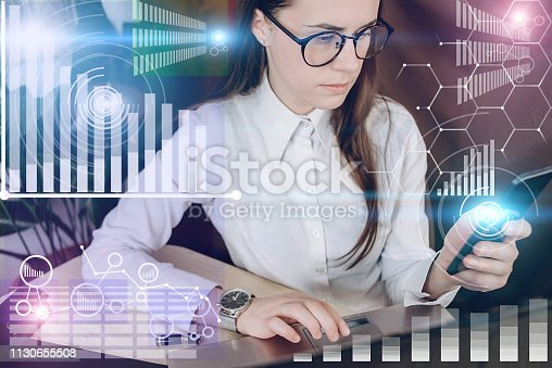 istock Woman in glasses working on a project in loft office. Woman develops marketing plan. Laptop and paperwork on the table. Statistic graph overlay, icon innovation interface 1130655508
