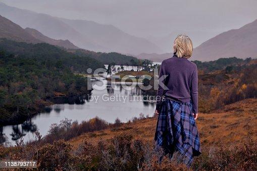 Senior woman wearing a tartan kilt in Glen Affric, Scotland.