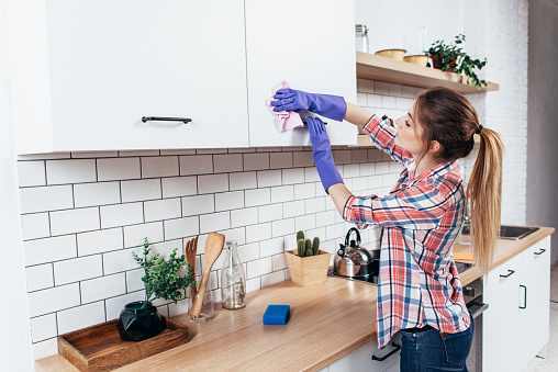 Woman In Gloves Cleaning Cabinet With Rag At Home Kitchen Stock Photo - Download Image Now