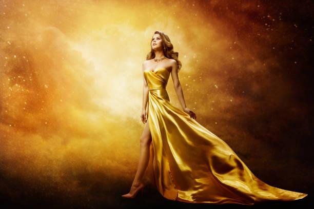 Woman in Gold Dress, Beautiful Fashion Model on Golden Night Sky stock photo