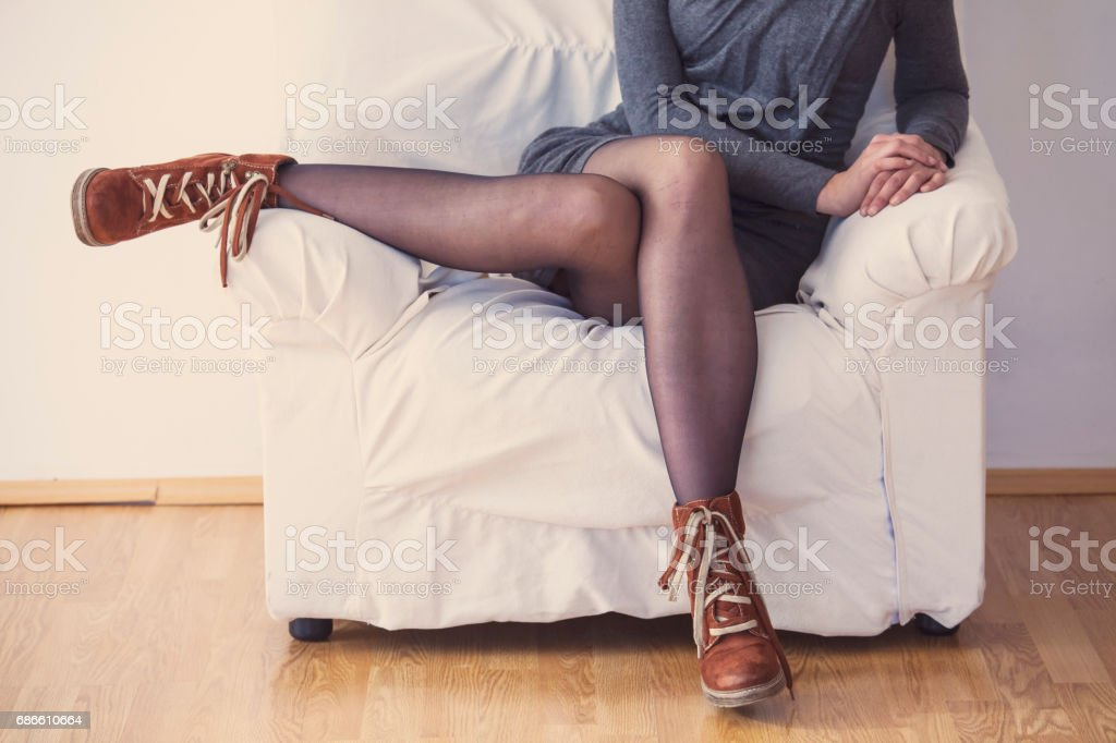 Woman in gray dress sitting legs crossed on armchair royalty-free stock photo