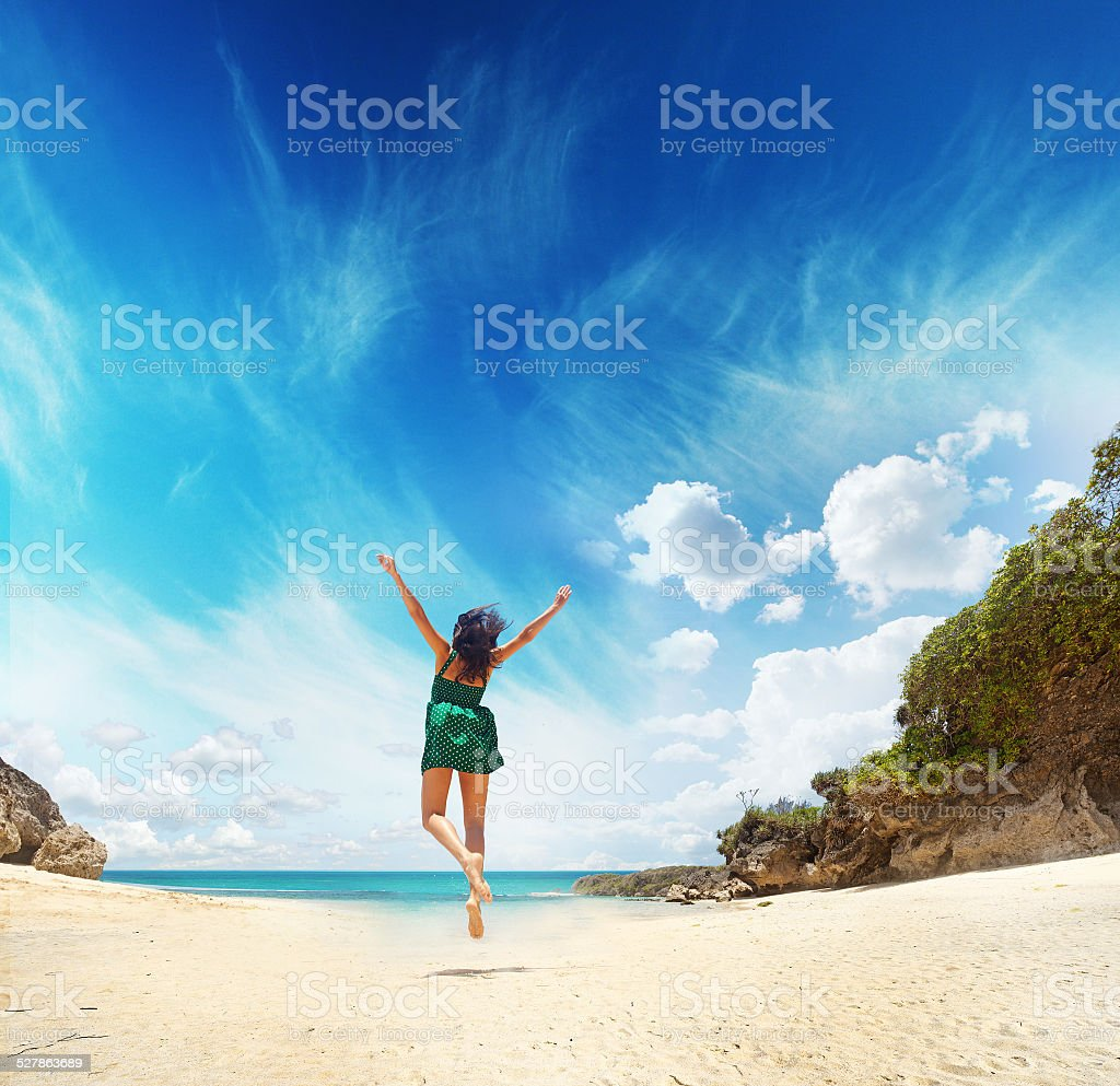 Woman in green dress on the beach stock photo