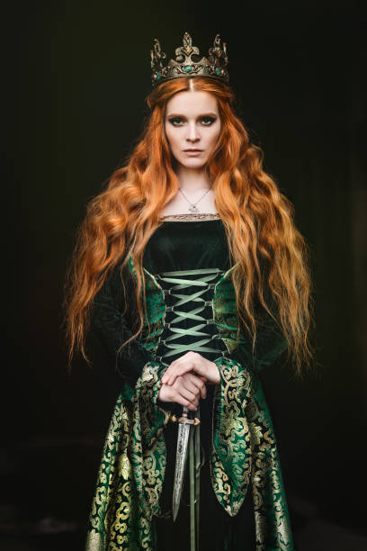 Woman in green medieval dress Portrait of a beautiful red-haired woman in green medieval dress costume stock pictures, royalty-free photos & images