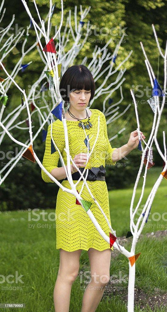 Woman in greenish or yellowish dress behind tree royalty-free stock photo