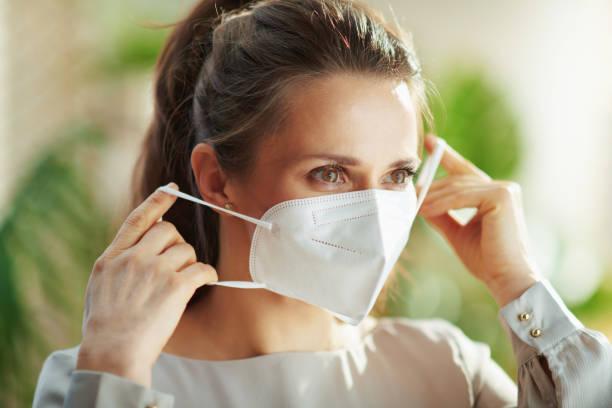 woman in grey blouse wearing ffp2 mask stock photo