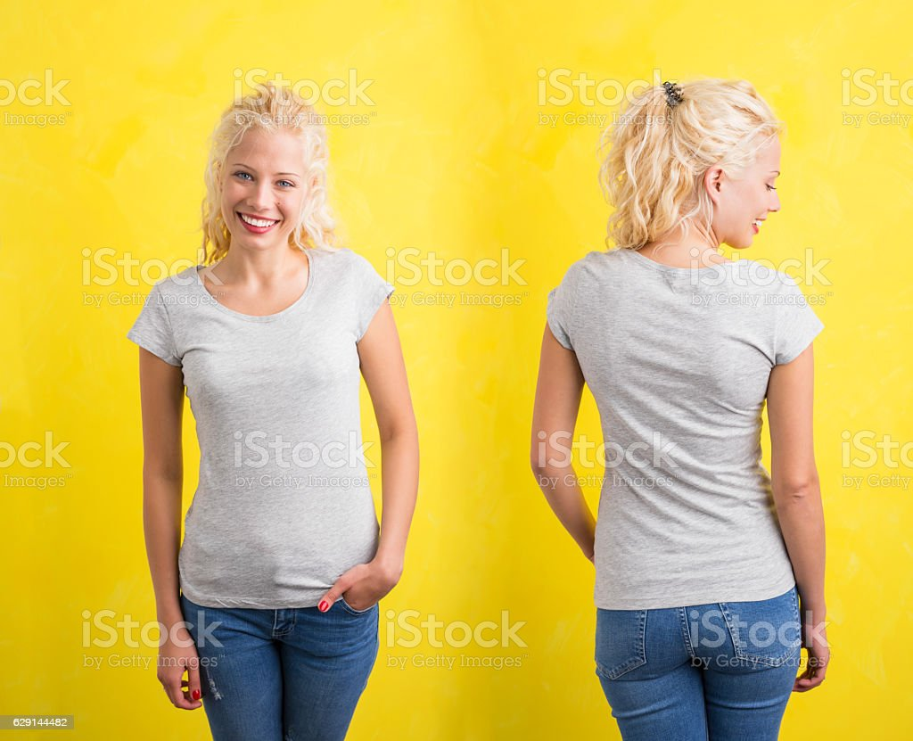 Woman in grey round neck T-shirt on yellow background stock photo