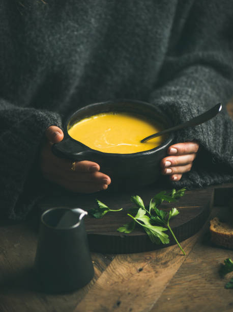 Woman in grey woolen winter sweater eating sweet corn soup Woman in dark grey woolen winter sweater eating sweet corn and shrimp chowder soup from black bowl. Autumn or winter warming food using mouth stock pictures, royalty-free photos & images