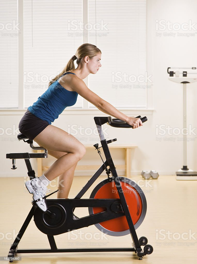 Woman in gym clothes focused on riding a stationary bicycle stock photo