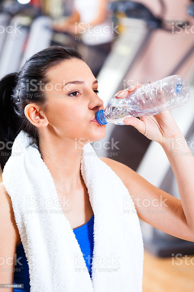 Woman in gym drinking water royalty-free stock photo