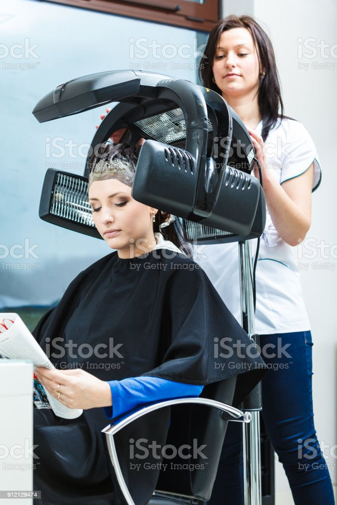 Haircare, relaxation and hairstyling concept. Woman sitting in black...