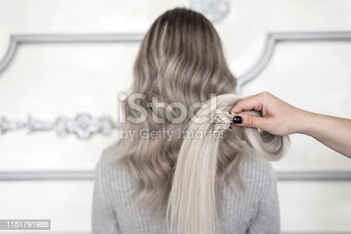 Cropped female hand showing sample of hair extension and in the background standing girl with blond ombre hairstyle