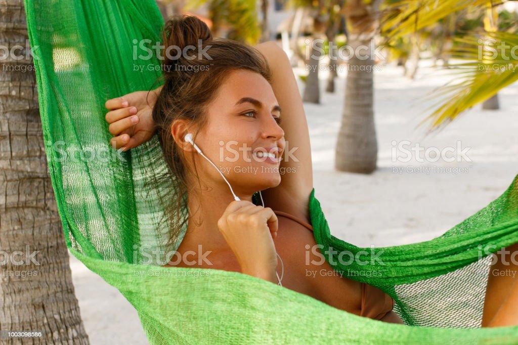 Mulher em rede na praia está escutando música ou audiobook - foto de acervo
