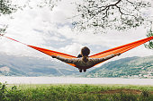 Young caucasian woman  in hammock on the background of fjord in Norway