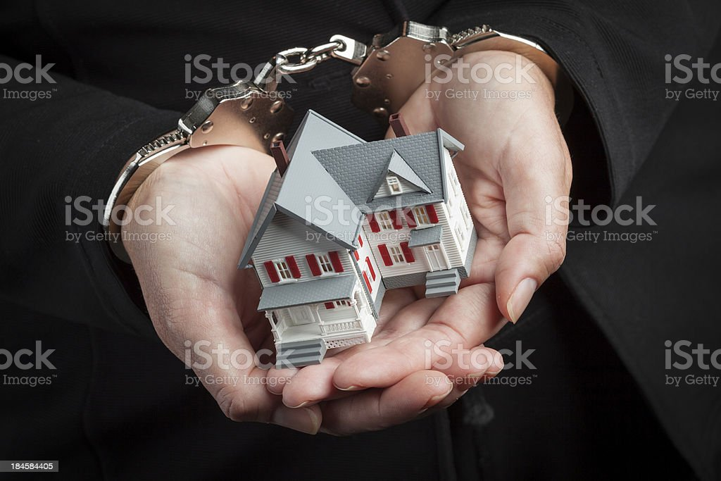 Woman In Handcuffs Holding Small House stock photo