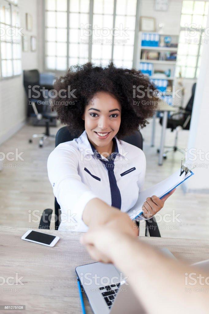 Femme dans la poignée de main au lieu de travail - Photo