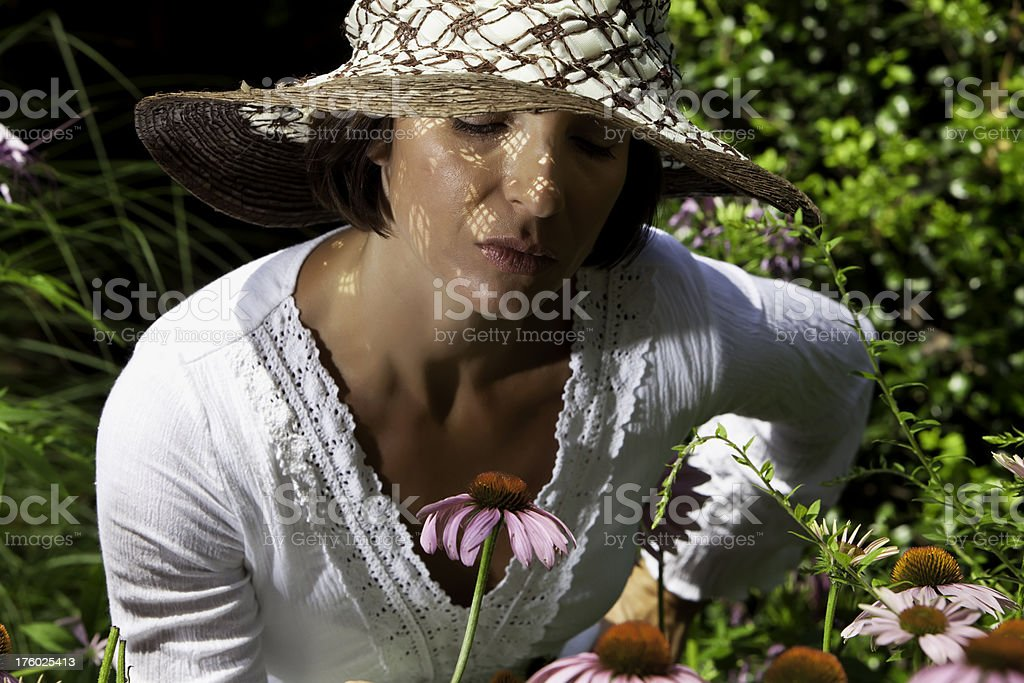 Woman in hat admiring flower royalty-free stock photo