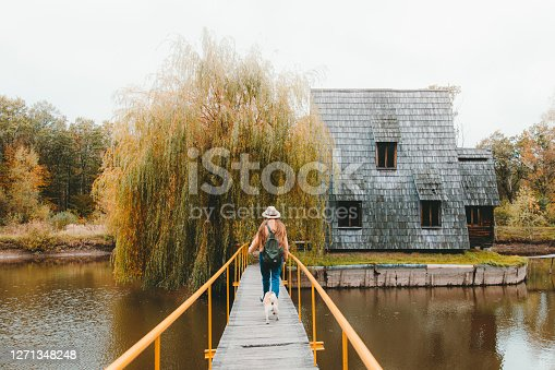 Young woman traveler with long hair and her small cute dog - pug breed enjoying the prefect autumn weekend walking at the bridge above the reflection lake to the abandoned triangle wooden fisherman cabin
