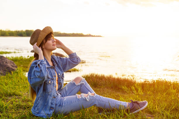 woman in hat and jeans sits on the background of the sea stock photo