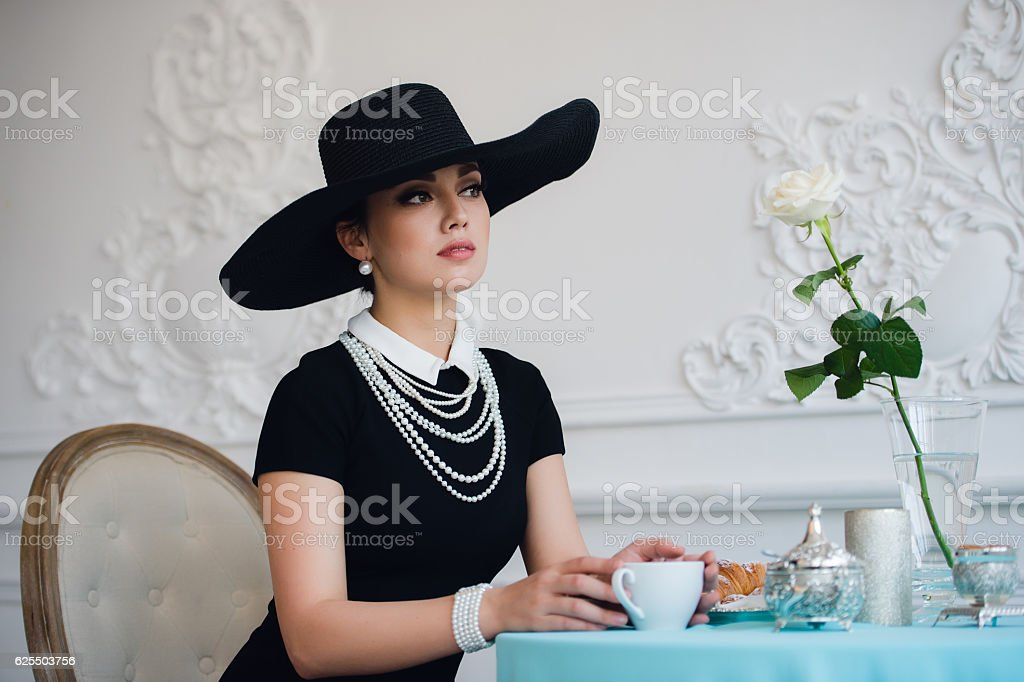 Woman in hat, much like the famous actress, croissant eating stock photo