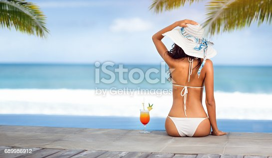 istock Woman in hat near the sea on beach with tropical cocktail 689986912