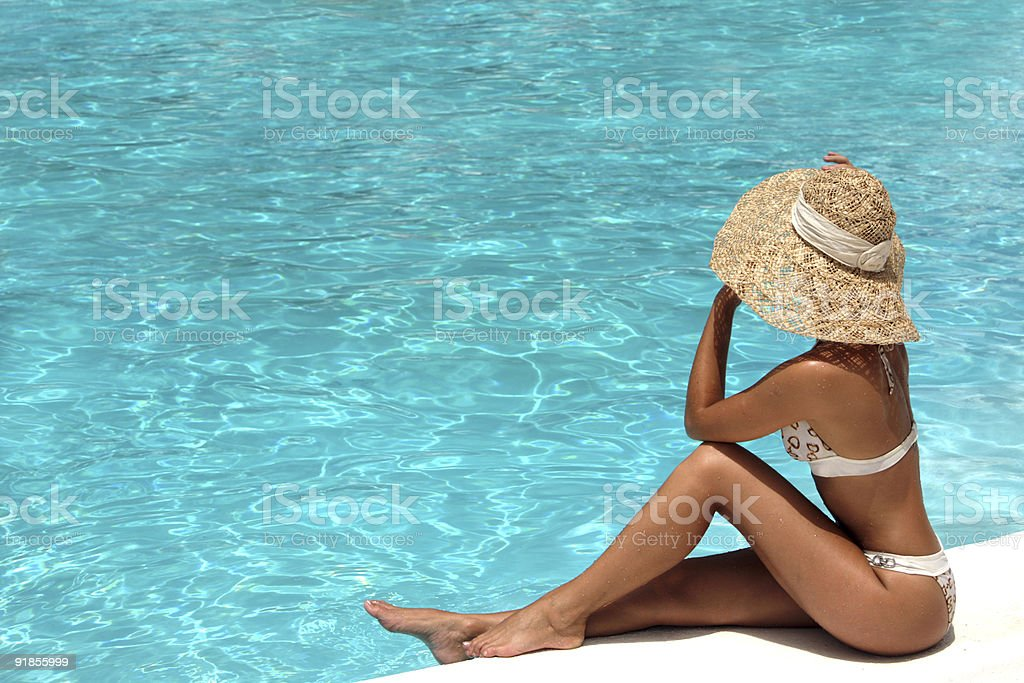 Woman in hat relaxing beside the pool royalty-free stock photo