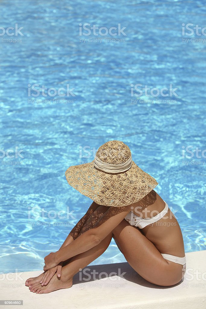 Woman in hat relaxing beside the pool stock photo