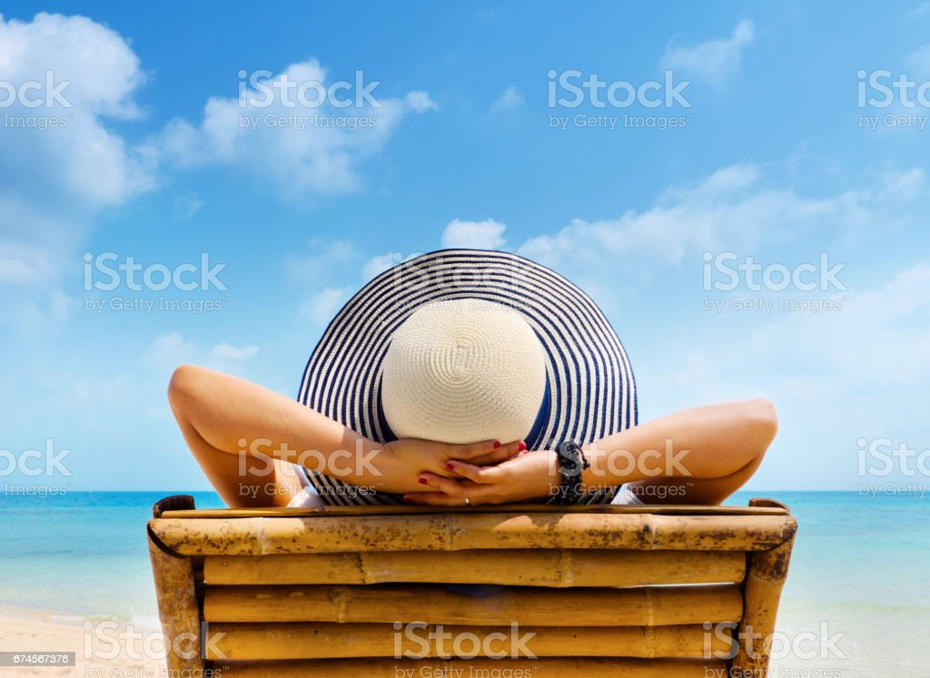 Woman in hat relaxing on beach, looking at sea. Copy space. stock photo