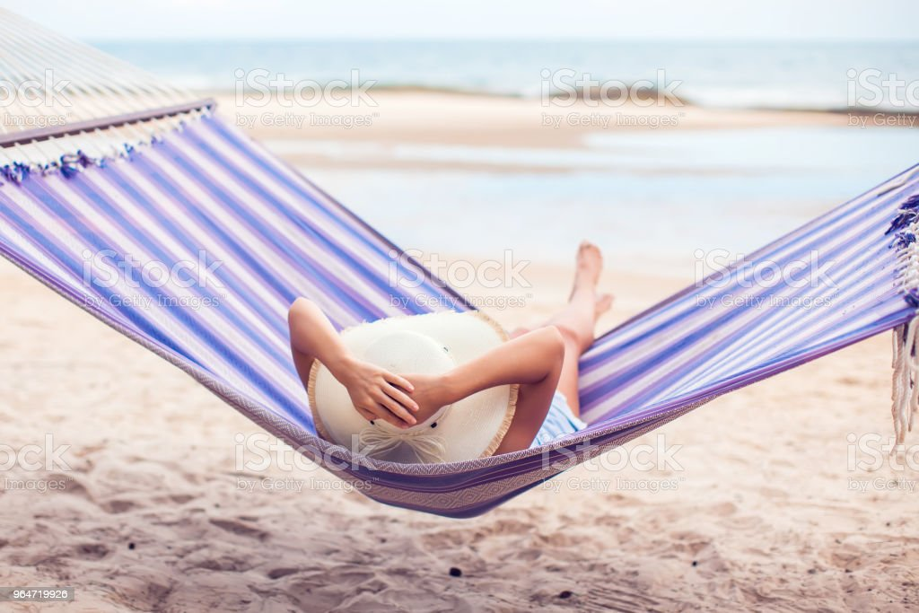 Woman in hat sitting in hammock on the beach. Travel and vacation concept. royalty-free stock photo