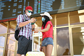 Woman in hat stand with man on train station and study schedule in phone and scoreboard with yellow suitcase. Two tourist stuck in country and can not return home because of coronavirus. Sale tourist permit to various countries of world.