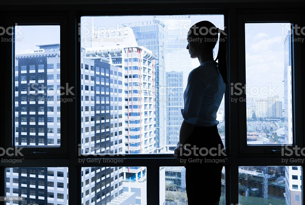 Woman in he office looking out the window. stock photo
