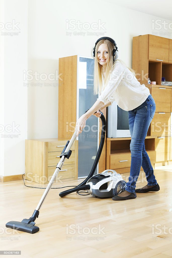 Woman in headphones cleaning with vacuum cleaner stock photo