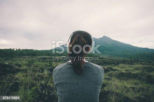 istock Woman in headphones listening music in nature 529415694