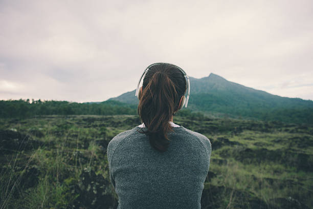 Woman in headphones listening music in nature stock photo